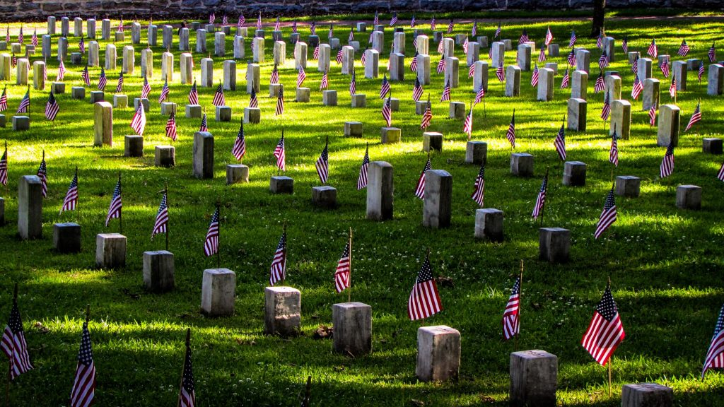 Rows of tombstones in a cemetery, each decorated with a miniature American flag.
