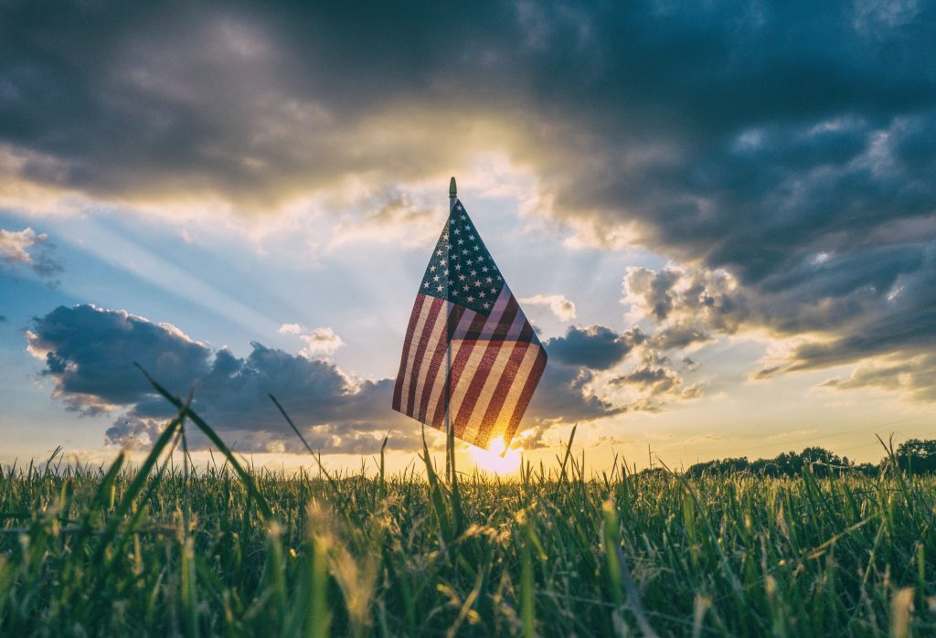 An American flag stands in an open field with the sun setting in the background.