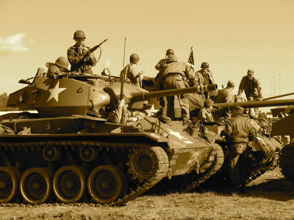 American soldiers are mounted on tanks circa WWII.